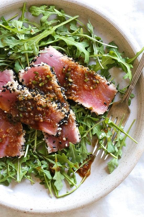 Sesame Crusted Tuna Steak on Arugula drizzled with a balsamic soy-ginger vinaigrette – yum!
