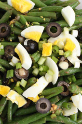 A cold string bean salad made with hard boiled eggs, olives and a balsamic vinaigrette.