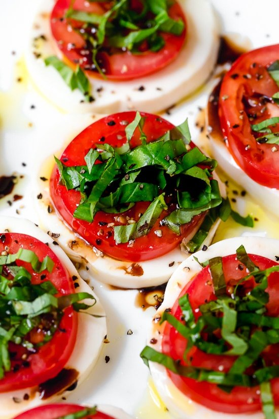 Caprese Salad or Insalata Caprese is a simple salad of fresh mozzarella and tomatoes topped with basil and a splash of balsamic. A perfect end of summer appetizer or side dish, especially when tomatoes are at their peak.