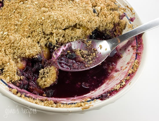 A round baking dish with blueberry peach crisp and a serving spoon