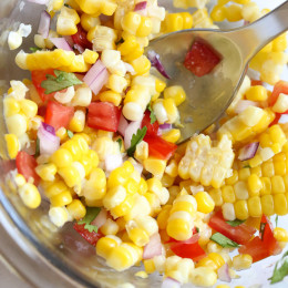 This easy corn salsa made with lime, cilantro and tomatoes are perfect with chips or served over your favorite tacos or burrito bowls!
