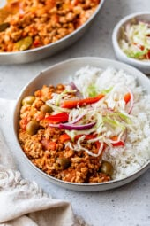 Turkey Picadillo with rice and slaw on a plate.