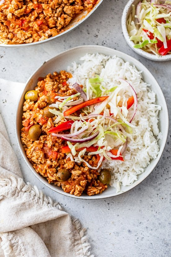 Picadillo with rice and slaw on a plate.