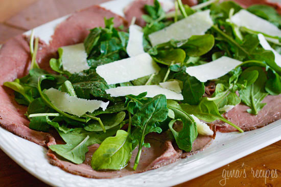 A platter with thin sliced roast beef, arugula and shaved asiago