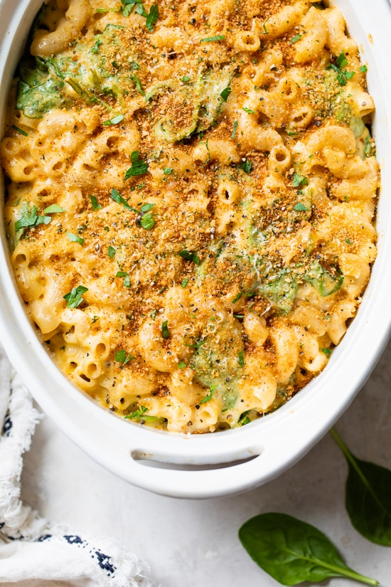 This creamy baked mac and cheese recipe is a lighter version of the classic recipe with added fiber from spinach. It's comfort food at it's finest!