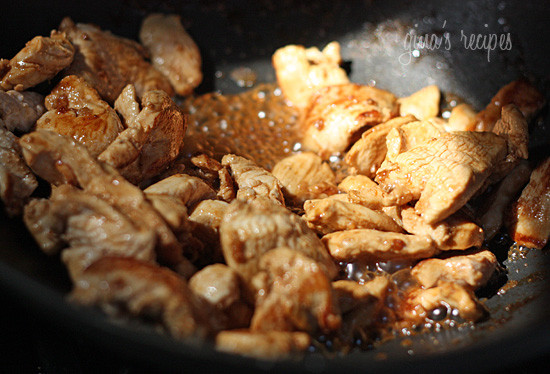 Seasoned chicken and oil sauteed in a wok on high heat.