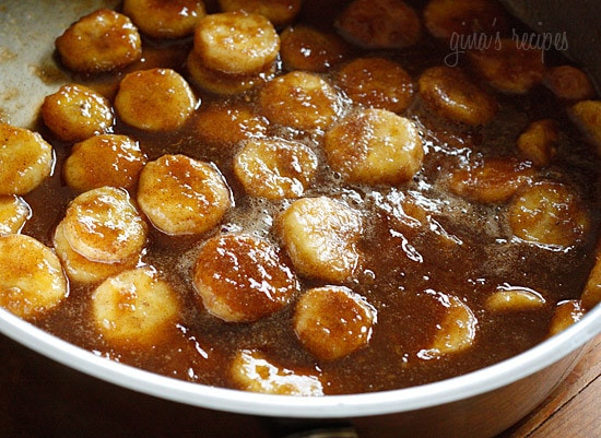 A deep skillet with banana slices cooking in brown sugar sauce