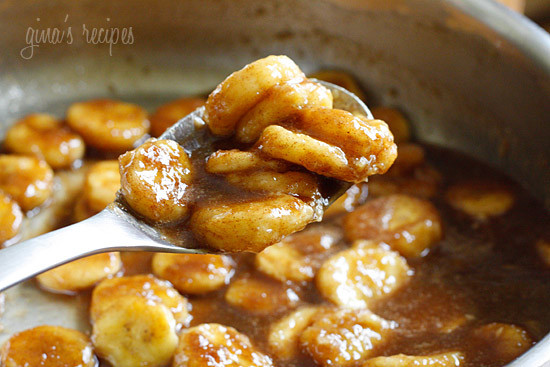 A spoonful of banana slices coated in brown sugar sauce over a saute pan full of banana slices and banana slices and sauce