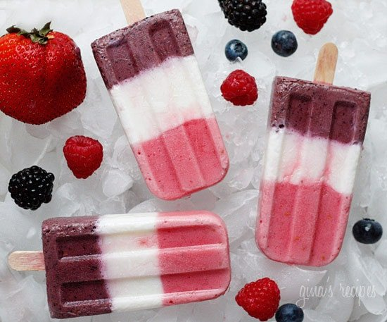 Three striped berry popsicles surrounded by fresh berries