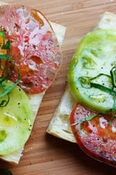 A juicy open faced summer tomato sandwich on crusty bread drizzled with extra virgin olive oil, a chiffonade of fresh basil, salt and fresh ground pepper. Simplicity at it's best!