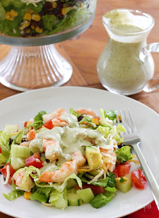 Mexican Shrimp Cobb Salad is a beautifully layered salad with shrimp, avocados, grilled corn, black bean salsa, cucumbers, tomatoes and cheese. This is delicious served this with creamy cilantro tomatillo dressing.