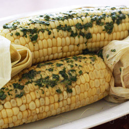 Sweet summer corn roasted in the oven and topped of with a light compound butter using fresh cilantro and a pinch of chipotle pepper and cumin.
