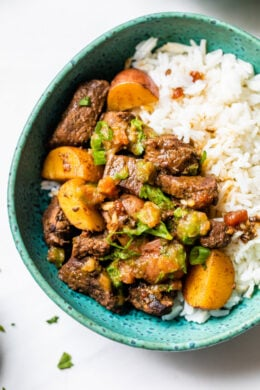 Carne Guisada or Latin Beef Stew is made with chunks of beef simmered in beer with scallions, garlic, tomatoes, cumin and cilantro.