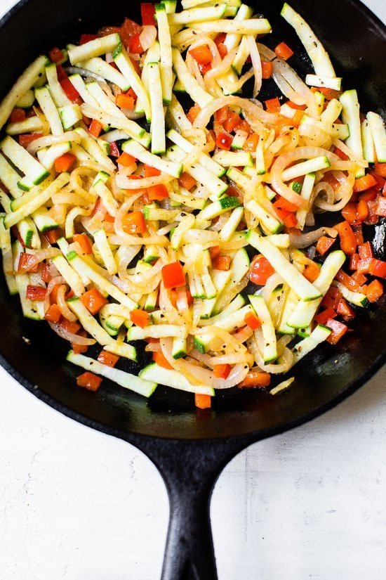 Caramelized Onion Red Pepper and Zucchini in a skillet.