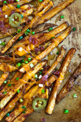 Guiltless cheesy baked seasoned fries topped with bacon, jalapeños and scallions... this is SOOO good! Pure comfort food when cheese fries are what you're craving.