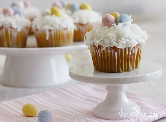 A quick and easy coconut cupcake made with a box white cake mix, light coconut milk and apple sauce. No butter, no oil necessary for this lower calorie cupcake recipe! Sweetened coconut flakes are combined with a light cream cheese frosting for a divine finish!