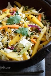 Light, fresh and crisp slaw made with shredded cabbage, carrots, lime juice, rice vinegar and a slightly under-ripe mango topped with sesame seeds. A perfect side to fish, pork and even burgers.