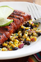 Grilled salmon steaks rubbed with a spicy blend of smoked paprika, chipotle chili powder, brown sugar, cumin and cocoa powder served with a quick side dish of black beans, grilled corn, cilantro and splash of lime juice.