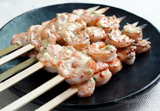 A plate of skewers with grilled shrimp covered with creamy chili sauce
