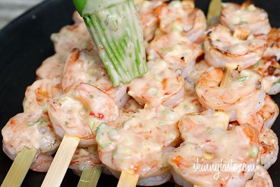 A plate of grilled shrimp on skewers being brushed with creamy chili sauce