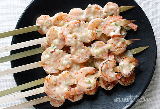 A plate of grilled shrimp on skewers with creamy chili sauce