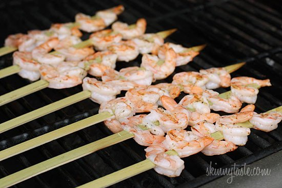 Skewers of shrimp cooking on a grill