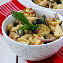 This warm pasta salad is big on summer vegetables, corn and zucchini, with a small kick of red pepper. A great sub to potato salad and a perfect meatless entree or side dish for your next picnic or family potluck.