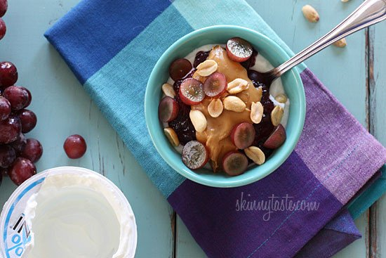 Peanut butter, grape jam, peanuts, and fresh red grapes on top of a bowl of yogurt... who needs the bread!