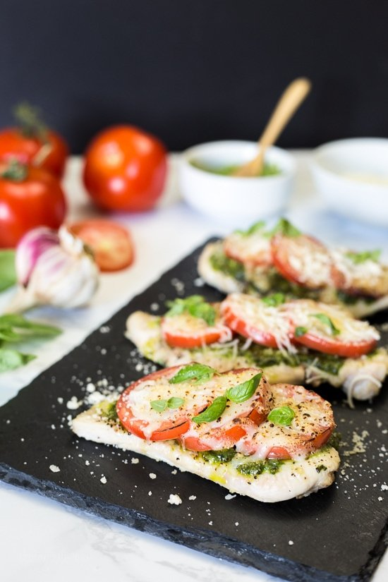 Chicken Pesto Bake is a simple, light dish made with skinless chicken breasts, pesto, tomatoes, mozzarella and Parmesan cheese. You can make this in the oven, or make it outside on the grill!