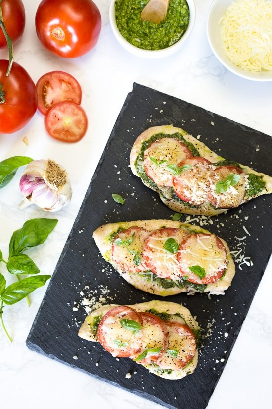 This easy Baked Pesto Chicken is a fast chicken dish made with skinless chicken breasts, pesto, tomatoes, mozzarella and Parmesan cheese. You can make this in the oven, or make it outside on the grill!