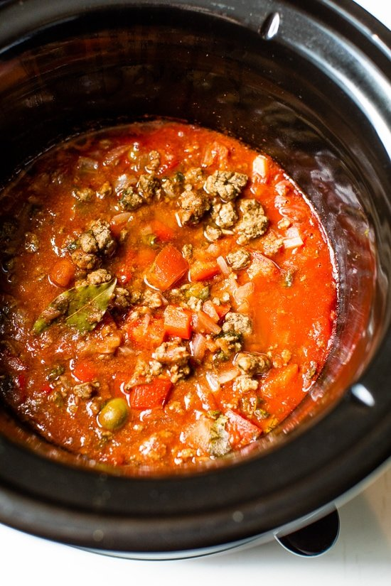 Crock Pot Picadillo is a flavorful Cuban dish made with ground beef and a sauce made from simmering tomatoes, green olives, bell peppers, cumin, and spices.