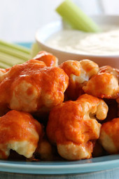 Hot and spicy cauliflower bites, battered and baked and smothered with hot sauce. Serve this with skinny blue cheese dressing and celery sticks on the side for a hot and spicy meatless appetizer.