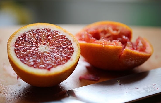 Two halves of a blood orange, with one half squeezed