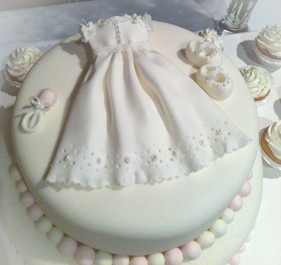 A white cake with a lacy baptism dress, baby shoes, and a rattle