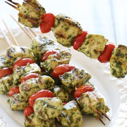 Grilled Pesto Chicken and Tomato Kebabs just SCREAM summer, made with chunks of boneless chicken breasts, skinny basil pesto and grape tomatoes. Serve this as an appetizer at your next backyard bash, or have them for dinner any night of the week with a great big salad or over pasta.