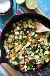 Mexican zucchini in a black cast iron skillet with a wooden spoon.