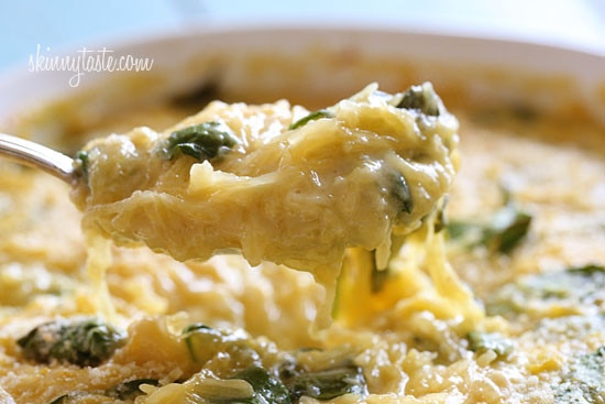 A bowl of creamy spaghetti squash with pieces of spinach