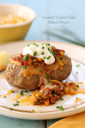 This loaded baked potato is stuffed with lean turkey chili, reduced fat shredded cheese and topped with some fresh chives – a quick, easy weeknight meal.