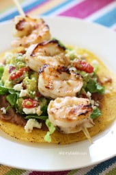 Grilled Shrimp Tostadas are SO good, layered with homemade guacamole, refried beans and lettuce on top of a crispy tostada.