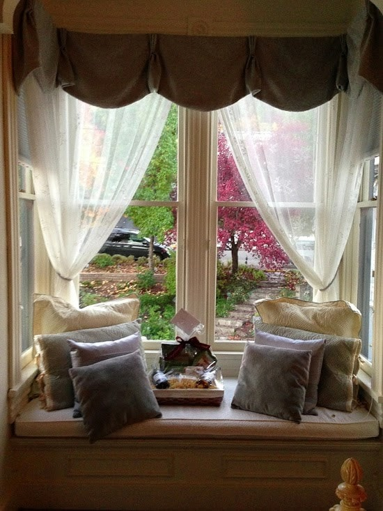 A window seat with sheer curtains, pillows and welcome basket with wine and snacks