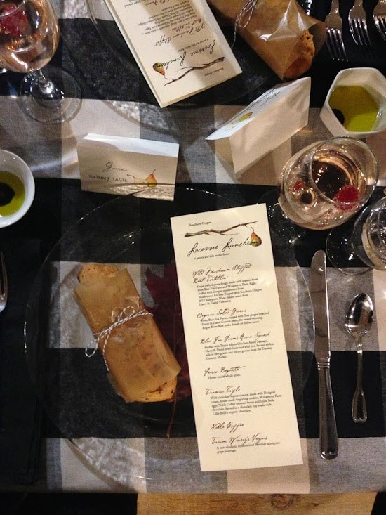 A place setting with clear glass plate, with a piece of bread wrapped in brown paper and a menu