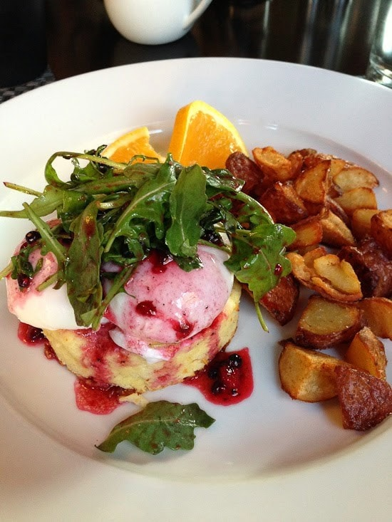 Poached eggs over souffle with arugula salad and berry dressing, a side of roasted potato chunks, and orange slices