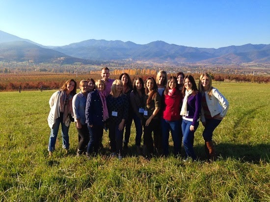 A group of friends in a field with fall foliage and mountains behind them