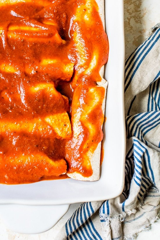Easy vegetarian enchiladas made with butternut squash and black beans, smothered with enchilada sauce and cheese, then baked in the oven. A delicious recipe that's perfect for meatless Mondays!