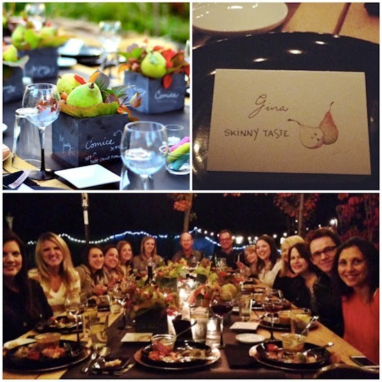 A tabletop with decorative boxes with pears and wine glasses, a name card for Gina from SkinnyTaste with a picture of pears, a group of 14 people around a large dinner table with plates of food and beverages