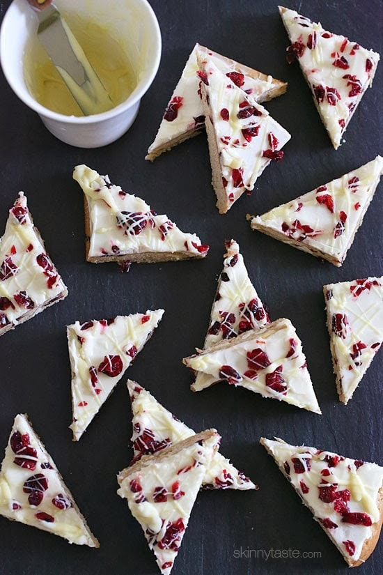 These Makeover Cranberry Bliss Bars are SO good, with more than half the calories and fat content from the ones you buy at Starbucks, and so much cheaper to make yourself! A blondie cookie bar with piles of white chocolate chips and dried cranberries, topped with sweet cream cheese, sour dried cranberries and white chocolate drizzle - perfect for the holidays!