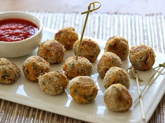 A plate of cooked mini spinach and sausage arancini balls with a bowl of marinara sauce