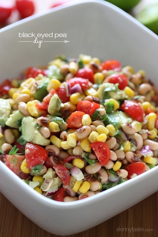 A bowl of black-eyed peas mixed with tomatoes, corn, avocado, and fresh cilantro