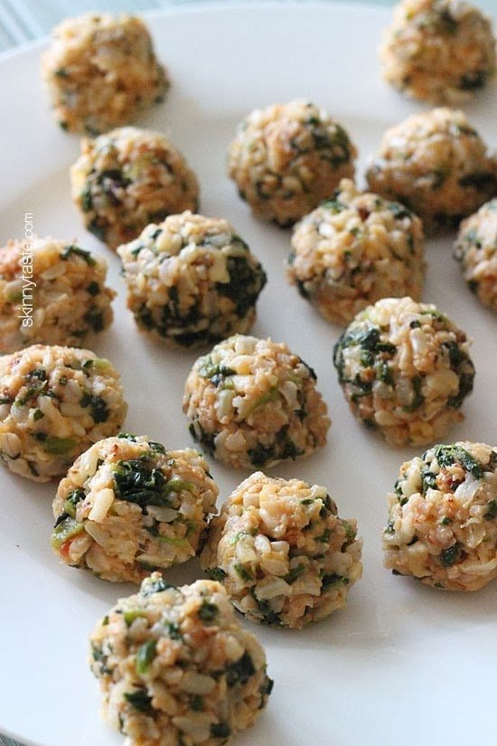 A plate of brown rice balls with crumbled sausage and pieces of spinach