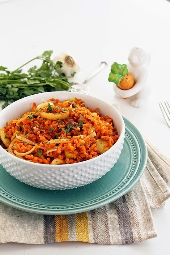 "While you dig your fork into this fluffy bowl of spiralized carrot ""rice"" leek risotto with bacon, you won't believe it's not real rice."